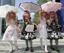 "Japanese women dressed in Lolita fashion walk in front of the venue of ""Individual Fashion Expo. IV"" fashion event in Tokyo"